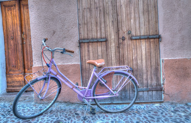 lilac bicycle in an old, paved street