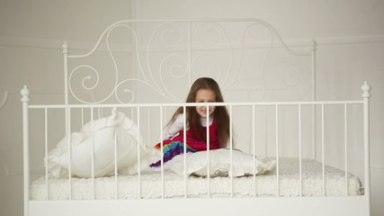 little girl playing with pillows on the big bed in the bedroom