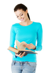 Happy brunette woman reading interesting book