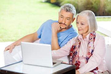 Male Caretaker And Senior Woman Using Laptop
