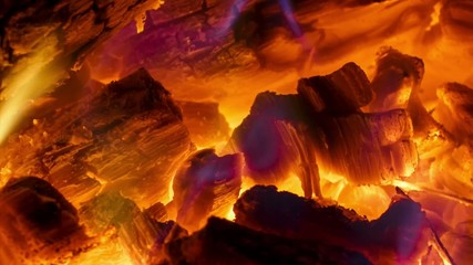 Close-up glowing coals in the fireplace with a blue flame