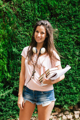 Young beautiful female standing outside with books and documents