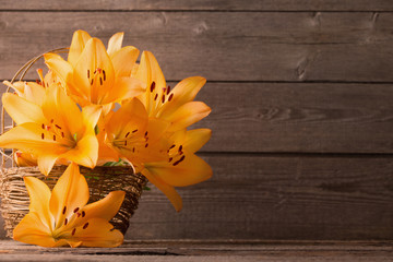 lily in basket on wooden background