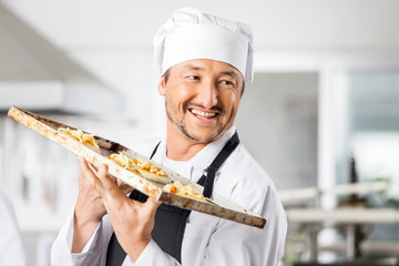 Happy Chef Holding Small Pizzas On Baking Sheet