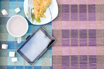 Piece of apple pie, cup of hot cocoa and tablet