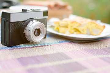 Piece of tasty biscuit apple pie and retro photo camera