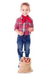 Happy little agriculturist boy showing potato harvest