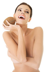Nude smiling woman with a coconut