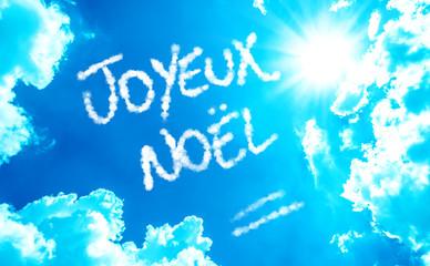 Happy Christmas (French: Joyeux Noel) written on a beautiful sky