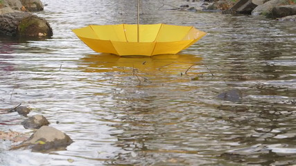 Yellow umbrella floating away on water in fall