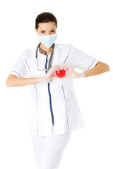 Doctor inprotecting mask holding heart model