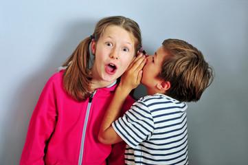 Junge flüstert Mädchen ins Ohr