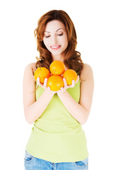 Happy woman holding oranges