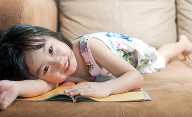 Asian little girl lying on her book