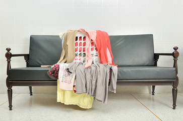 a lot of clothes scattered in the basket on a sofa
