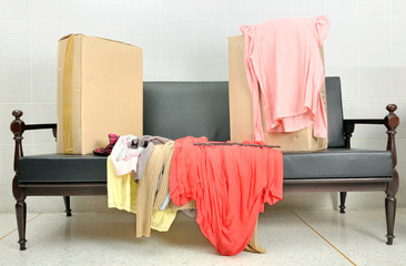 cardboard boxes and stack of clothes on a sofa