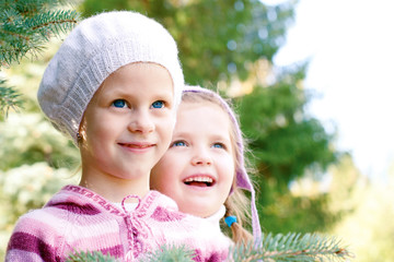 two children in colorful knitted clothing hugging