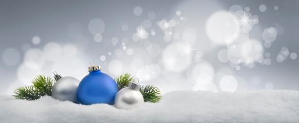 Blaue und silberne Weihnachtskugeln im Schnee