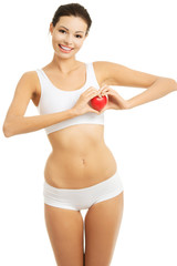 Young woman in underwear holding a heart model