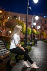 girl is sitting on the bench in the park - night