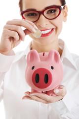 Woman in eyewear putting money to piggybank