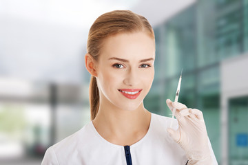 Beautiful young doctor or nurse is holding a needle.