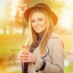Beautiful young woman with fedora and takeaway coffee outdoors