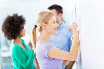 Woman writing ideas on adhesive notes