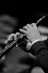 Hands of man playing the oboe in black and white