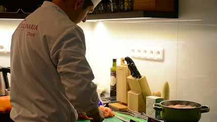 chef cooks food in the kitchen (home) - chef slicing fish
