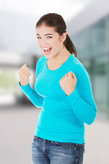 Excited happy success young woman with fists up