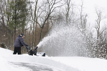 Man Using Snow Blower to Clear Snow