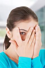 Shy teenage girl peeking through covered face