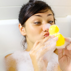 Woman having fun with yellow duck in bathtub