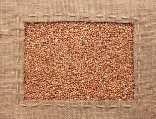 Frame made of burlap with the line lies on  buckwheat  grains