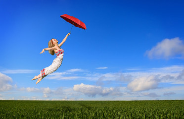 Beautiful young woman flying on a green meadow with red umbrella