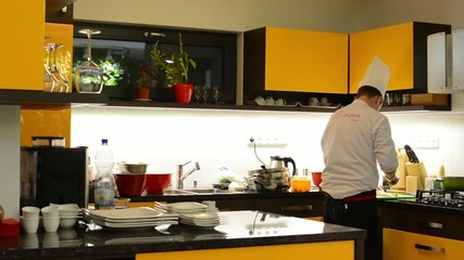 chef cooks food in the kitchen (home)