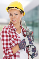 Young woman in protective helmet and jackhammer.