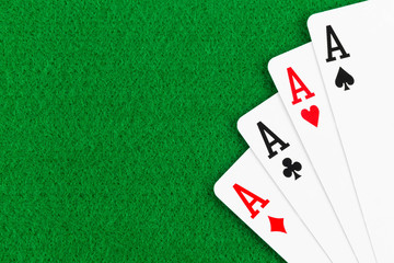 Four aces poker playing card on green felt background
