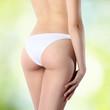 Leinwanddruck Bild - female buttocks in white panties on a green background