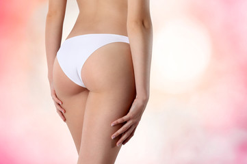 female buttocks in white panties on a pink background