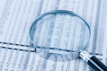 Magnifier rest on stock price detail financial newspaper