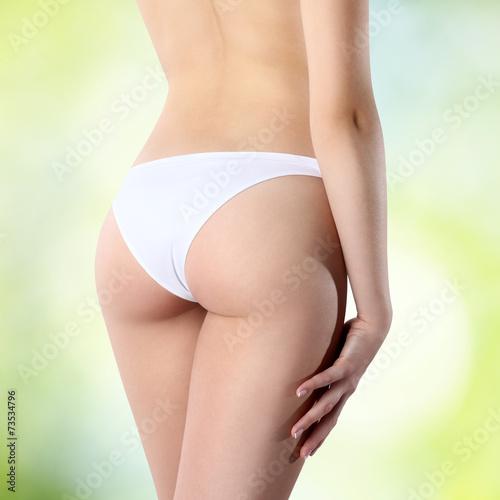 Leinwanddruck Bild female buttocks in white panties on a green background