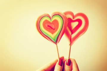 Colorful heart shaped lollipops in woman hand