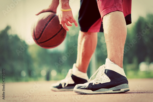 Poster Young man on basketball court dribbling with bal