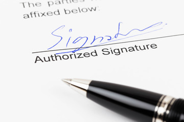 Signature on document with pen