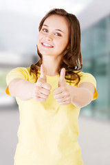 Teen woman in casual clothes gesturing thumbs up.