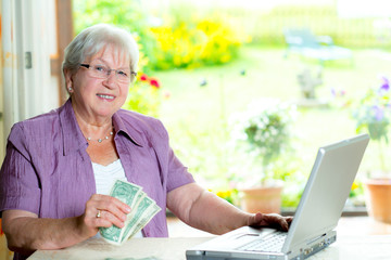 older woman with money and computer looking friendly