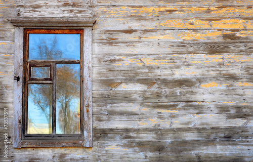 wall of the old wooden house with window