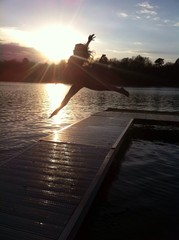 Girl jumping with arms stretched at the lake.